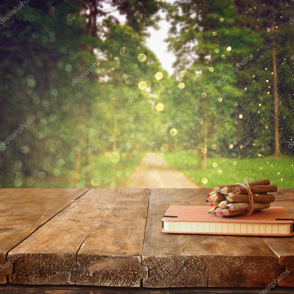 abstract image of vintage notebook and stack of wooden colorful pencils on wooden texture table in front of countryside forest view