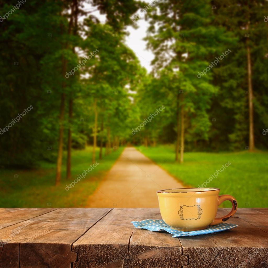 front image of coffee cup over wooden table and autumn leaves in front of autumnal forest background.