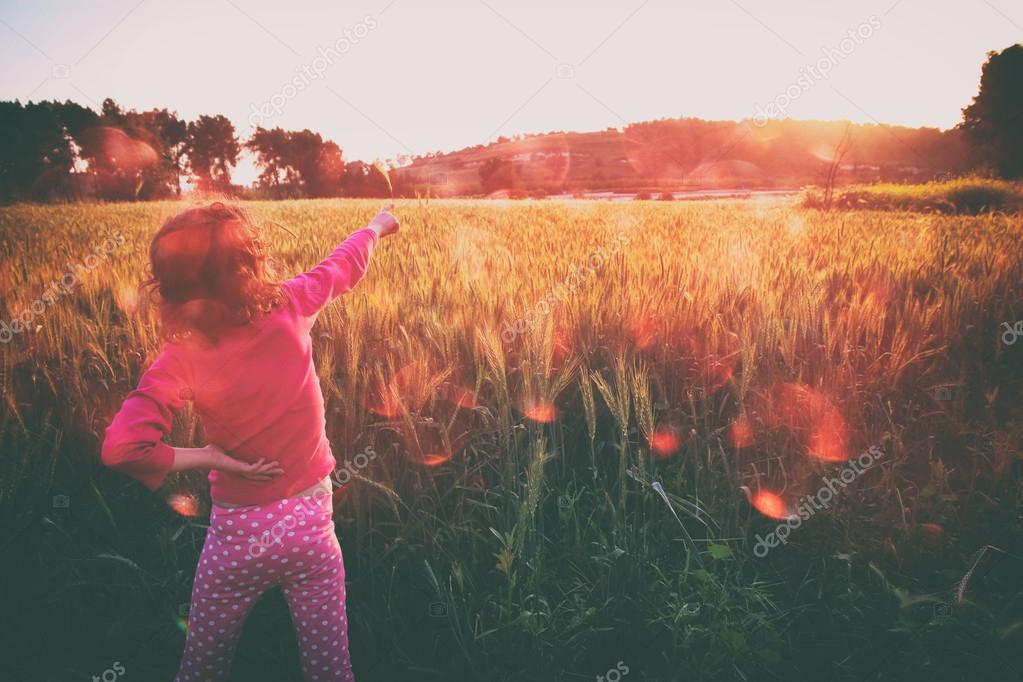cute kid (girl) standing in field at sunset with hands stretched looking at the landscape. instagram style image with bokeh lights. freedom and happiness  concept.