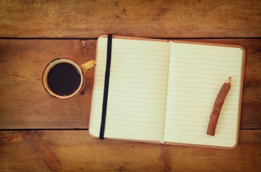 blank open vintage notebook, old paper and wooden pencil next to cup of coffee over wooden table. ready for mockup.