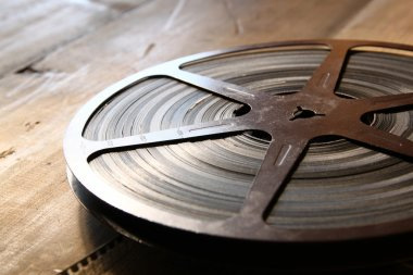 image of old 8 mm movie reel over wooden background. retro style image.