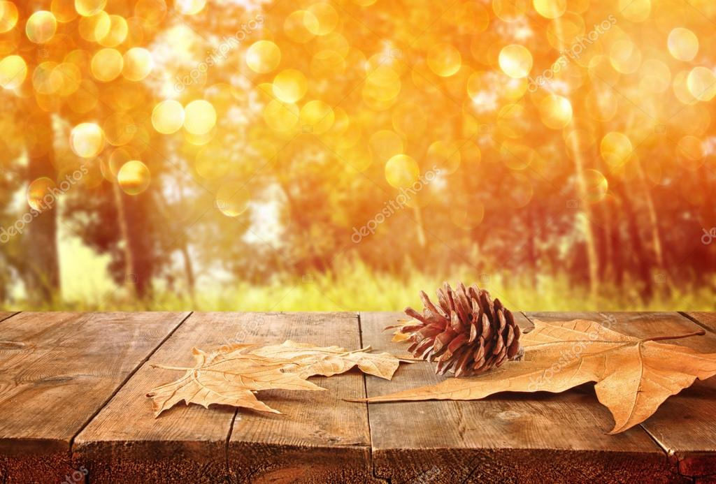 autumn background of fallen leaves over wooden table and forest backgrond with lens flare and sunset.