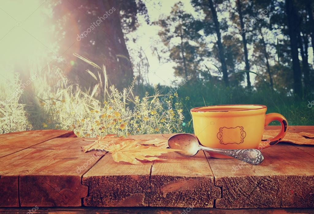 front image of coffee cup over wooden table and autumn leaves in front of forest background . retro style image.
