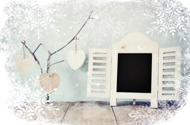 decorative chalkboard frame and wooden hanging hearts over wooden table. ready for text or mockup. retro filtered image with snowflakes overlay.