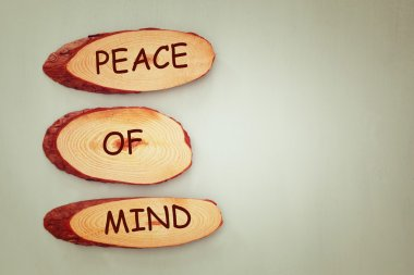 top view image of wooden signs with the text peace of mind.