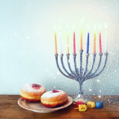 image of jewish holiday Hanukkah with menorah (traditional Candelabra), donuts and wooden dreidels (spinning top). retro filtered image.
