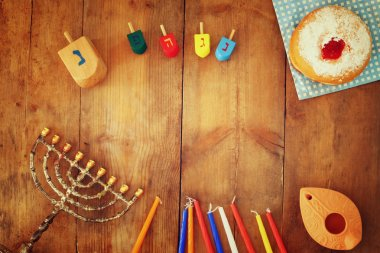 top view image of jewish holiday Hanukkah with menorah (traditional Candelabra), donuts and wooden dreidels (spinning top). retro filtered image.