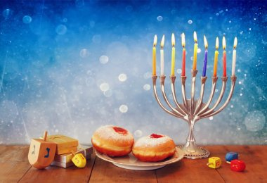 low key image of jewish holiday Hanukkah with menorah, doughnuts and wooden dreidels (spinning top). retro filtered image.