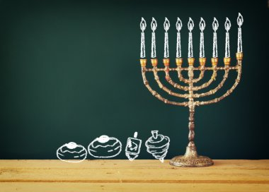 image of jewish holiday Hanukkah with drawing menorah candles (traditional Candelabra), donuts and dreidels (spinning top) over chalkboard background.