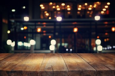 image of wooden table in front of abstract blurred background of resturant lights.