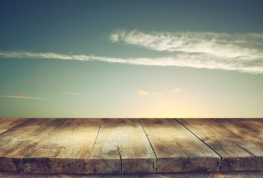 image of textured wood table in front of beach landscape at sunset time.