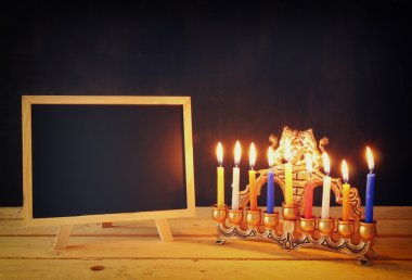 low key image of jewish holiday Hanukkah with menorah (traditional Candelabra) and wooden chalkboard , room for text.