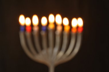 Abstract blurred background of jewish holiday Hanukkah background with menorah (traditional candelabra) Burning candles over black background.
