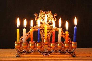 Image of jewish holiday Hanukkah background with menorah (traditional candelabra) Burning candles over black background.