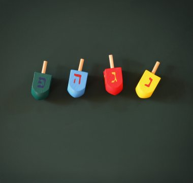 Image of jewish holiday Hanukkah with wooden colorful dreidels (spinning top) over chalkboard background. room for text.