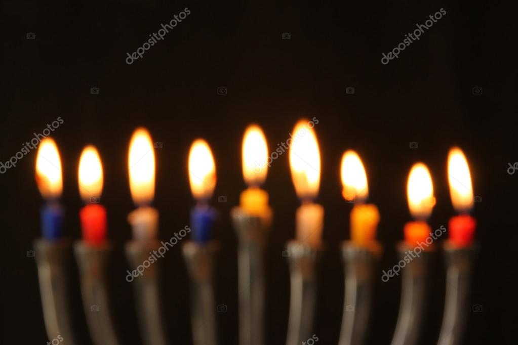Abstract Blurred Background Of Jewish Holiday Hanukkah With Menorah Traditional Candelabra Burning Candles Over Black