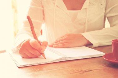 young woman near window writing