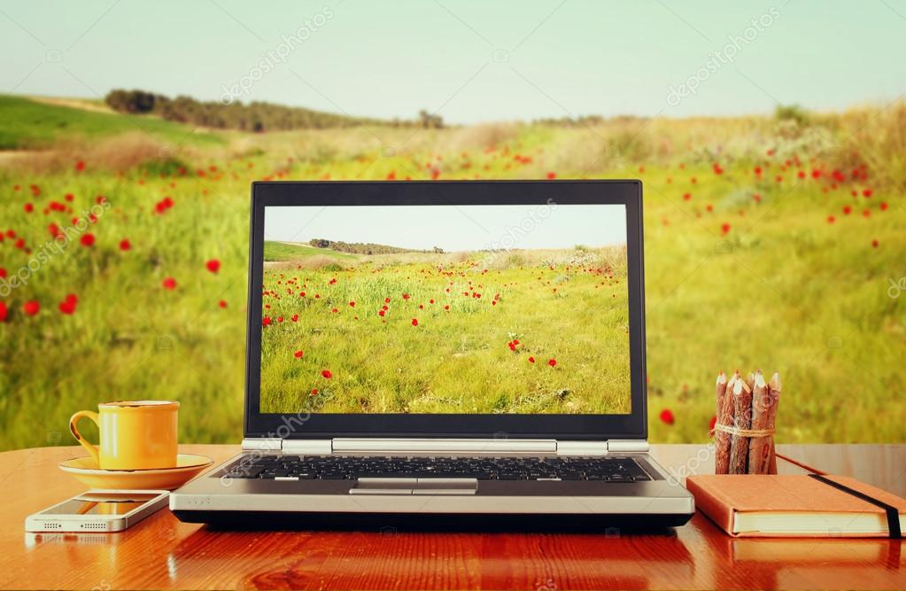 laptop over wooden table outdoors