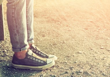 close up image of girl in sneakers sitting on the bench
