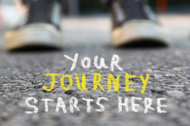 image with selective focus over asphalt road and person with handwritten text - your journey starts here. education and motivation concept.