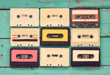 close up photo of vintage cassette tape over aqua wooden table . top view. retro filtered.