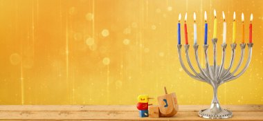 website banner image of of jewish holiday Hanukkah with menorah (traditional Candelabra). retro filtered. glitter overlay.