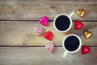 top view image of colorful heart shape chocolates and couple mugs of coffee  on wooden table. valentine's day celebration concept.