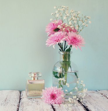 vintage perfume bottle next to white flowers on wooden table