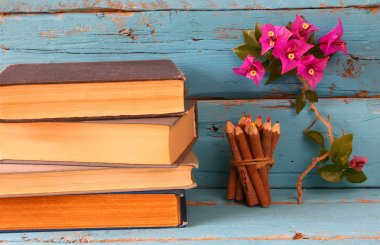 stack of old books next to colorful pencils and bougainvillea flower on wooden table. vintage filtered image