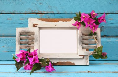 vintage blank frame next to beautiful purple mediterranean summer flowers. template, ready to put photography