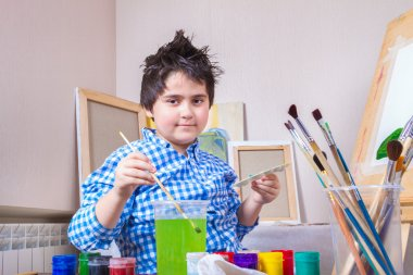 The boy draws paint brush and rinse dirty