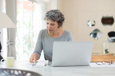 Senior woman checking bills