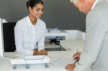 Businessman signing employee sheet