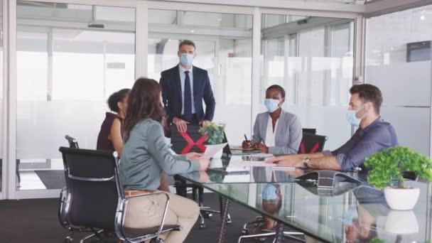 Skupina multietnických podnikatelů při setkávání s obličejovou maskou v konferenční místnosti během pandemie covid19. Formální obchodní pracovníci diskutují o strategii při nošení masek a udržování sociálního odstupu v zasedací místnosti. Nová normalita a obchodní život.