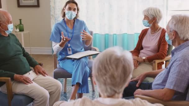 Group of senior people listening to nurse wearing face mask for safety. Counselor wearing surgical mask talking to group of senior people educating them about vaccine symptoms. Psychological support group for elderly and lonely people.
