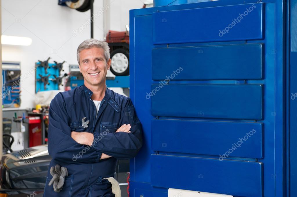 Happy Mature Mechanic In Garage