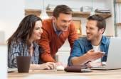 Šťastní kolegové pracují společně na laptop