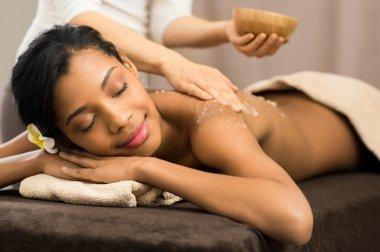 Applying scrub salt on  woman back