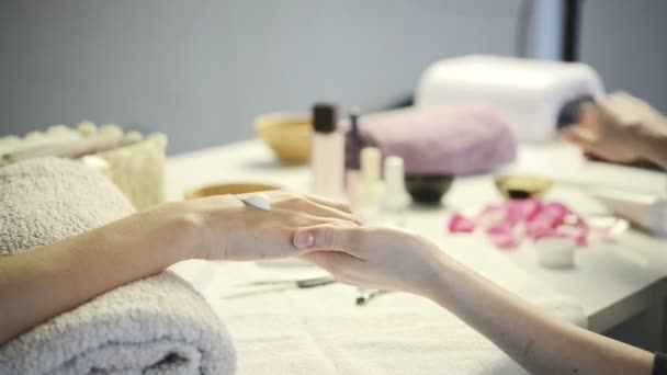 beautician applying hand moisturizer to a customer