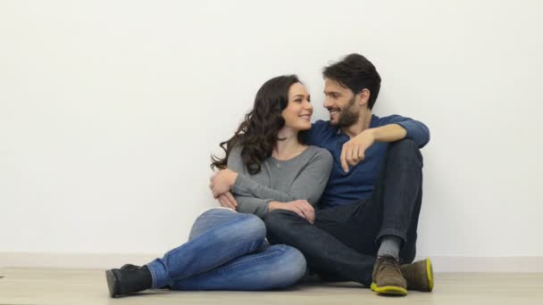 Šťastný mladý pár sedí na podlaze
