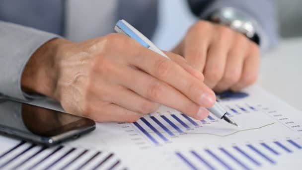 Hand with pen and financial documents