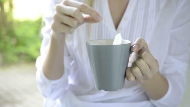 Žena, namáčení sáček čaje do šálku s horkou vodou
