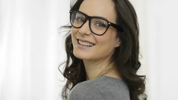 Usměvavá mladá žena nosí dioptrické brýle