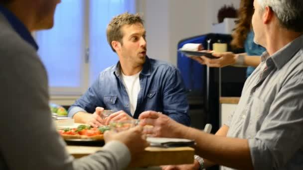 Žena sloužící talíř sýrů s muži v kuchyni