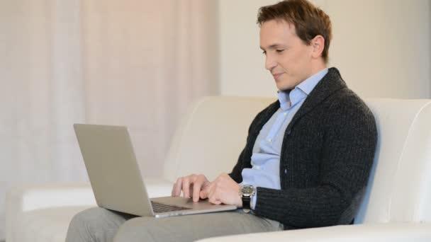 Boldog ember pihentető a kanapén használ laptop