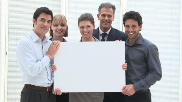 Happy business team holding a blank placard