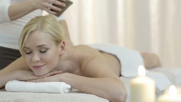 Žena receving olej na masáž v salonu krásy