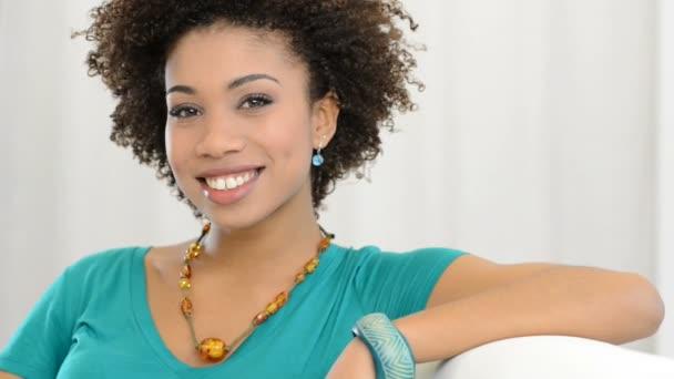 Africká dívka s úsměvem, sedí na gauči