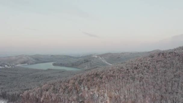Drone flight over a winter forest and a highway among the hills in the evening