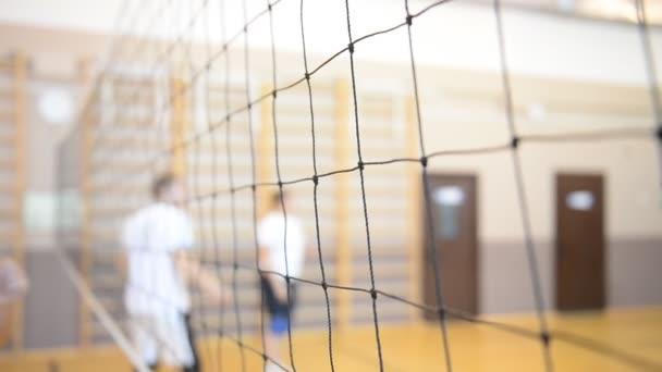 Hrát volejbal v tělocvičně. Closeup mřížky